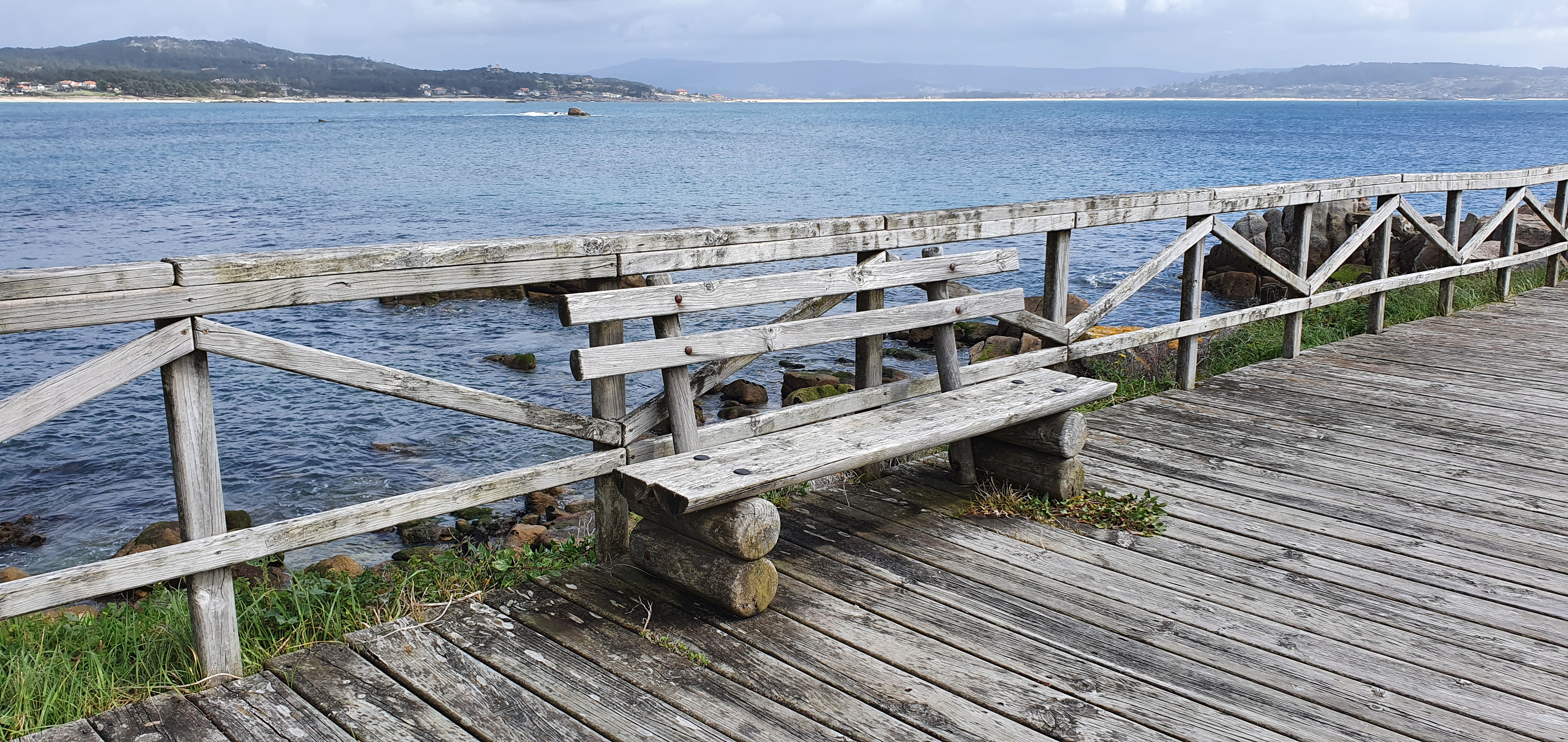 Wooden bench on a boardwalk by the sea