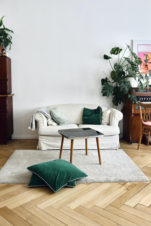 green throw pillow on white sofa