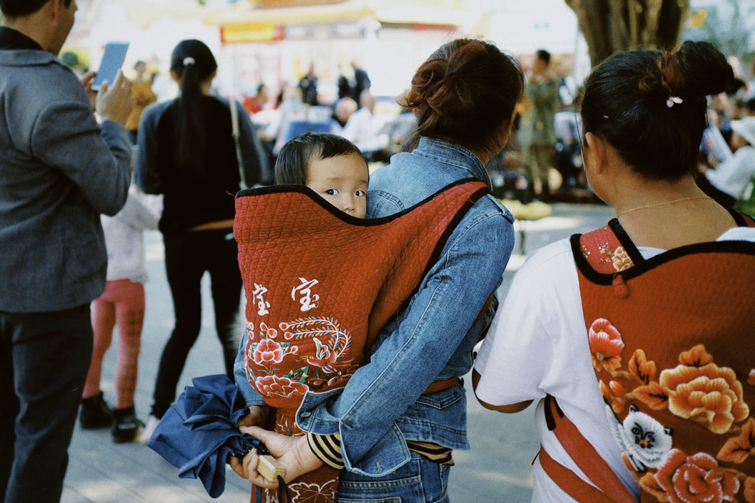 woman in blue denim jacket carrying baby in orange and white shirt