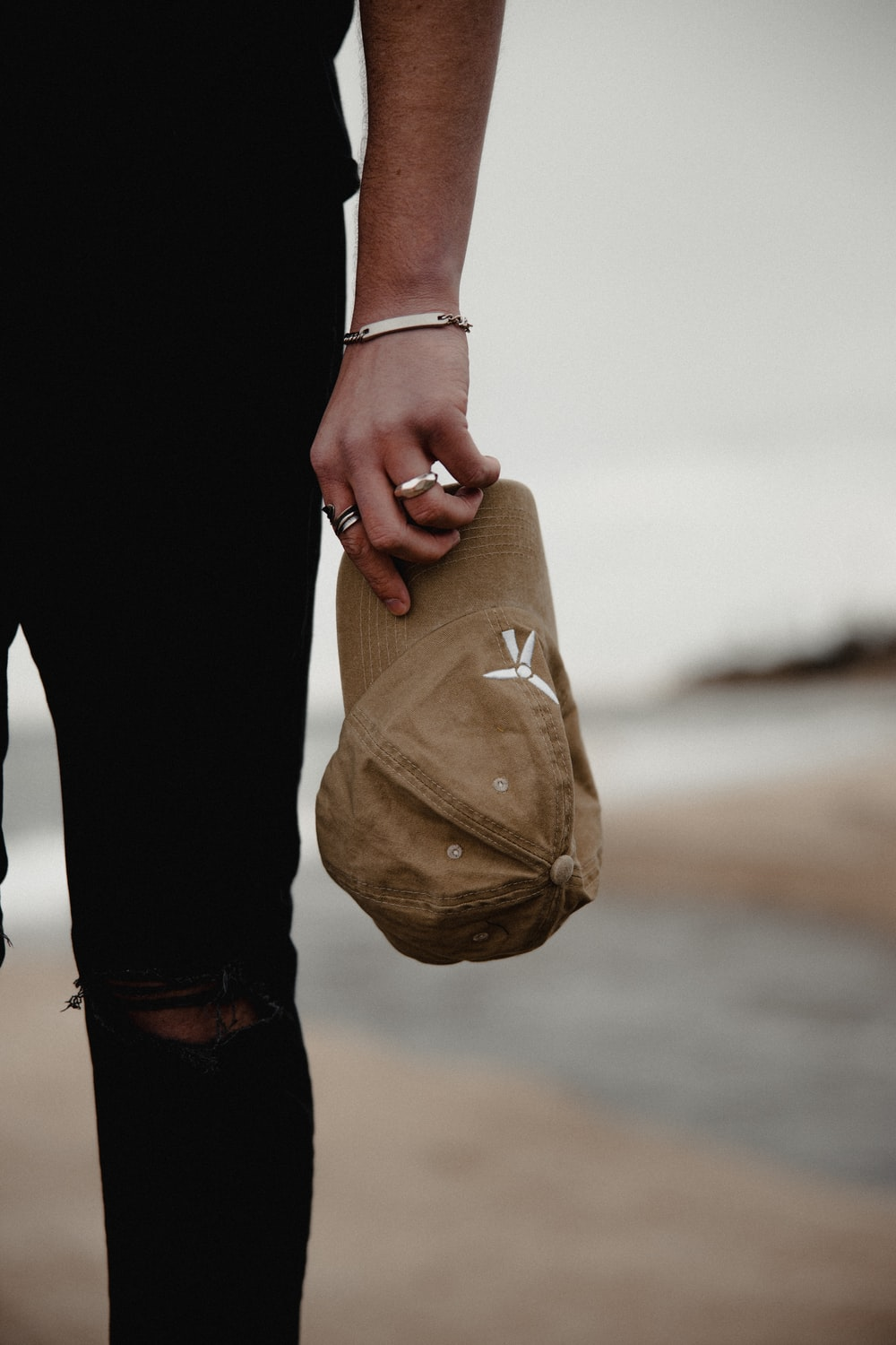 person in black pants holding brown paper bag
