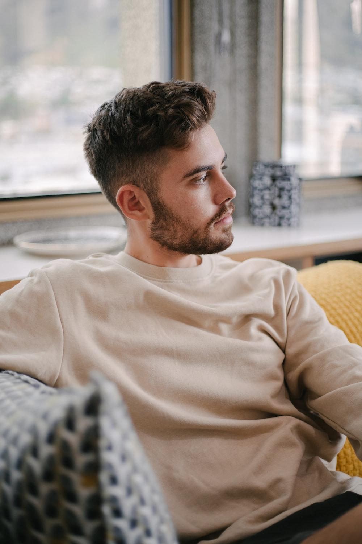 man in white crew neck long sleeve shirt sitting on yellow sofa