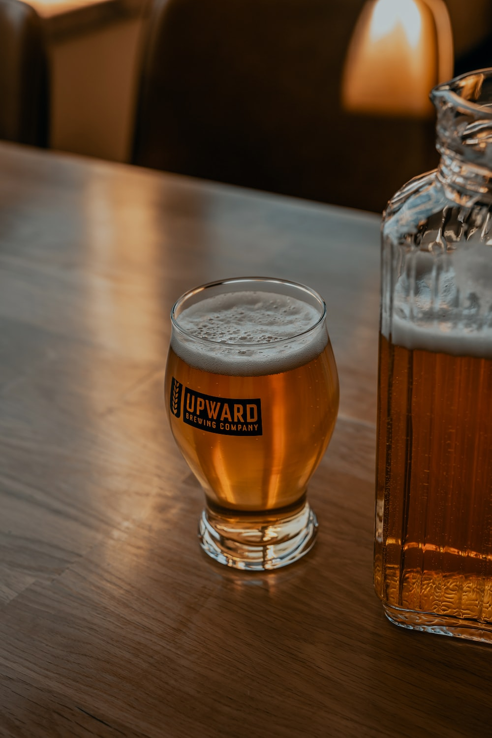 clear drinking glass with beer on brown wooden table