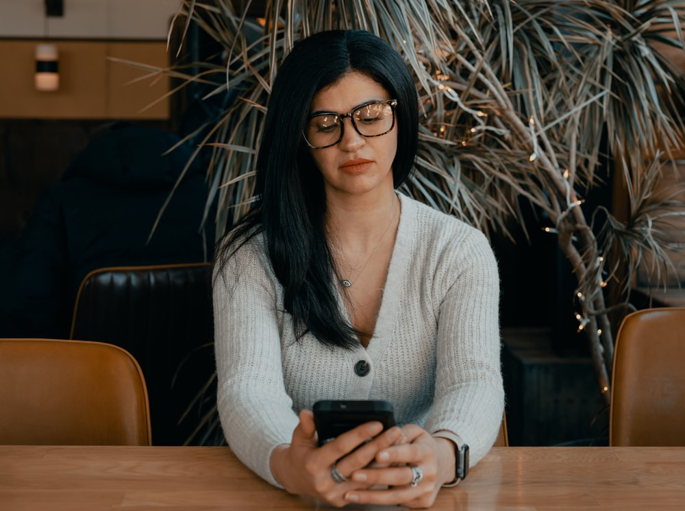 woman in white cardigan holding black smartphone
