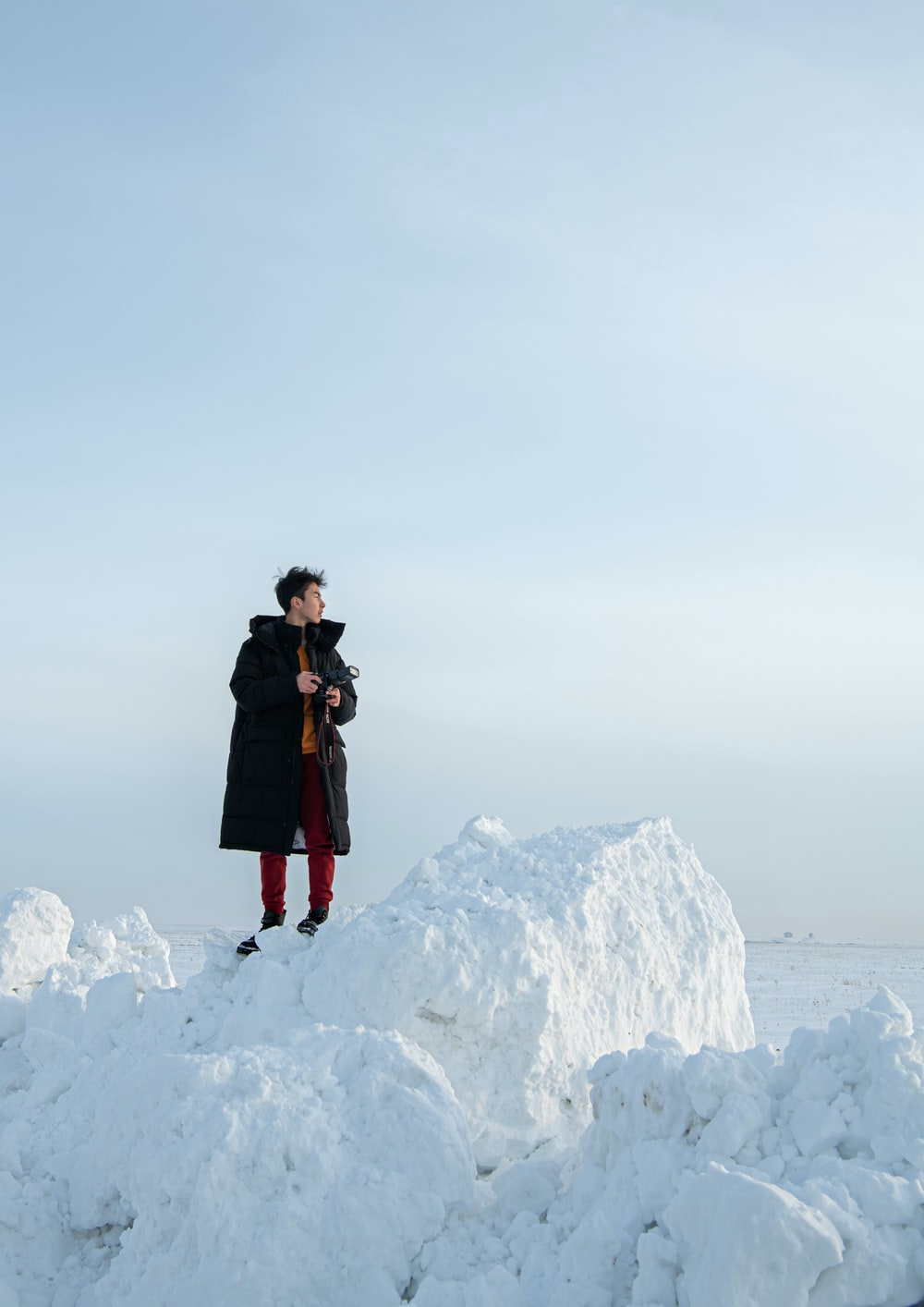 woman in black coat standing on white snow covered mountain during daytime