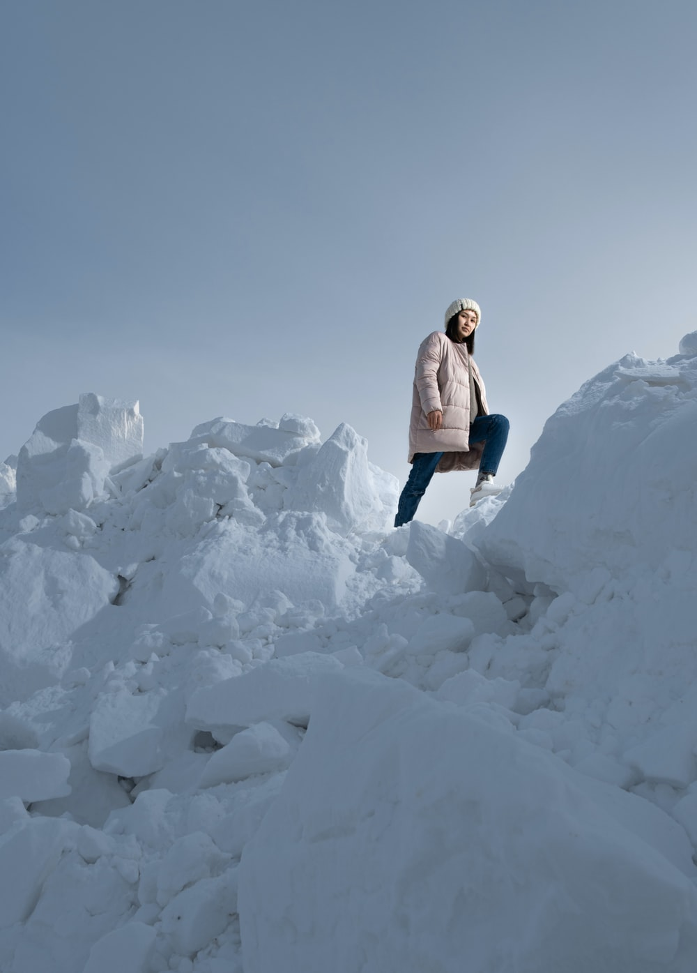 woman in white jacket and blue denim jeans standing on white snow covered ground during daytime