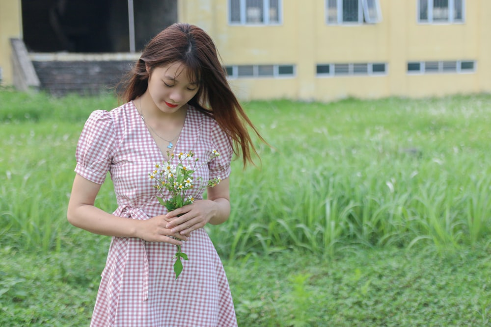 woman in white and red dress standing on green grass field during daytime
