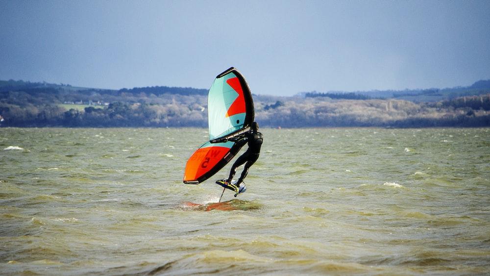 man in black wet suit riding orange kayak on sea during daytime
