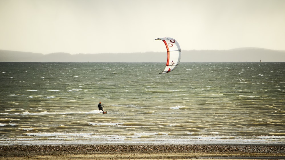 person in black shirt and black shorts holding white and red kite surfing on sea during