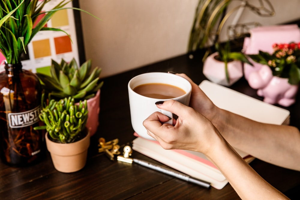 person holding white ceramic mug on white book page