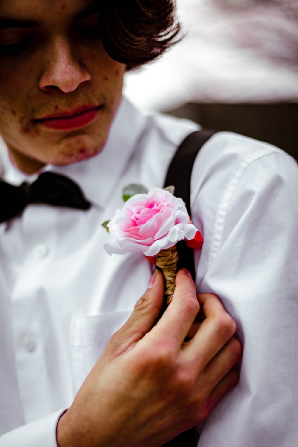 man in white dress shirt with black bowtie holding pink rose