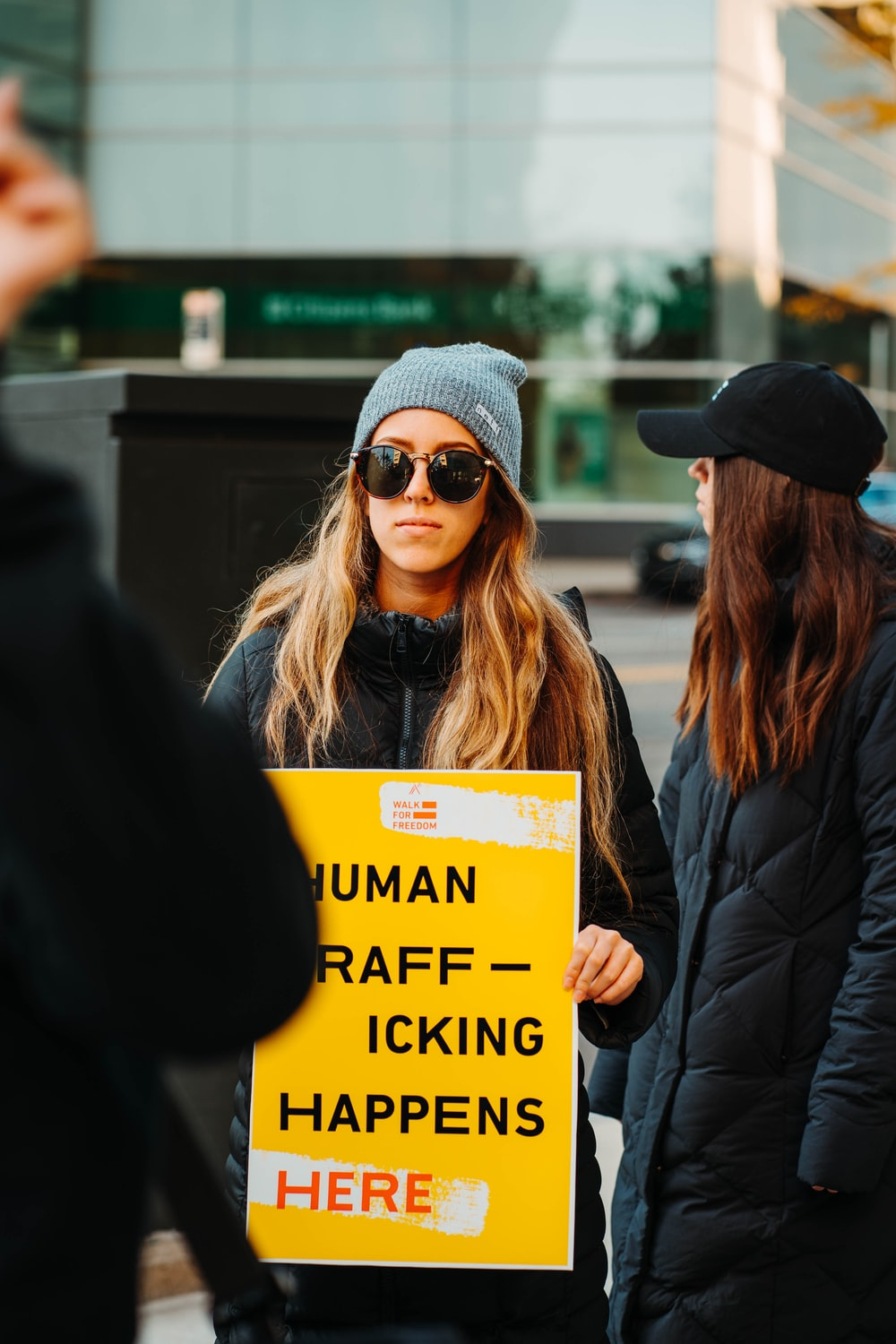 woman in black jacket wearing black sunglasses holding yellow and black signage