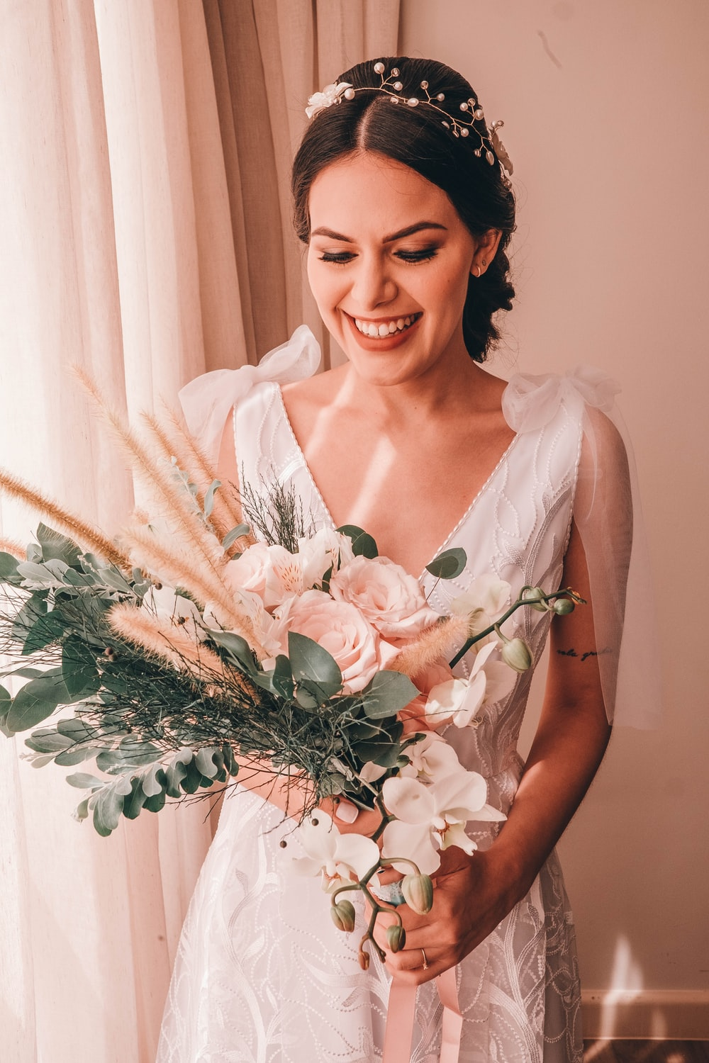woman in white sleeveless dress holding white flower bouquet