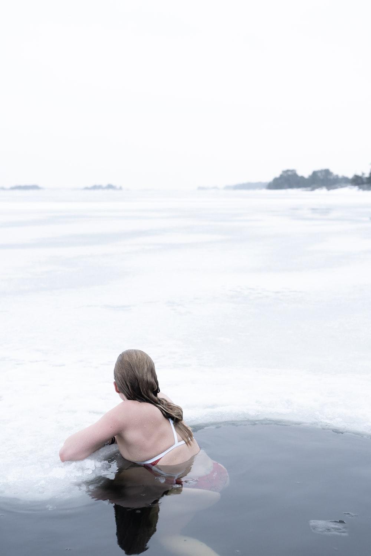 woman in black bikini top standing on white sand during daytime