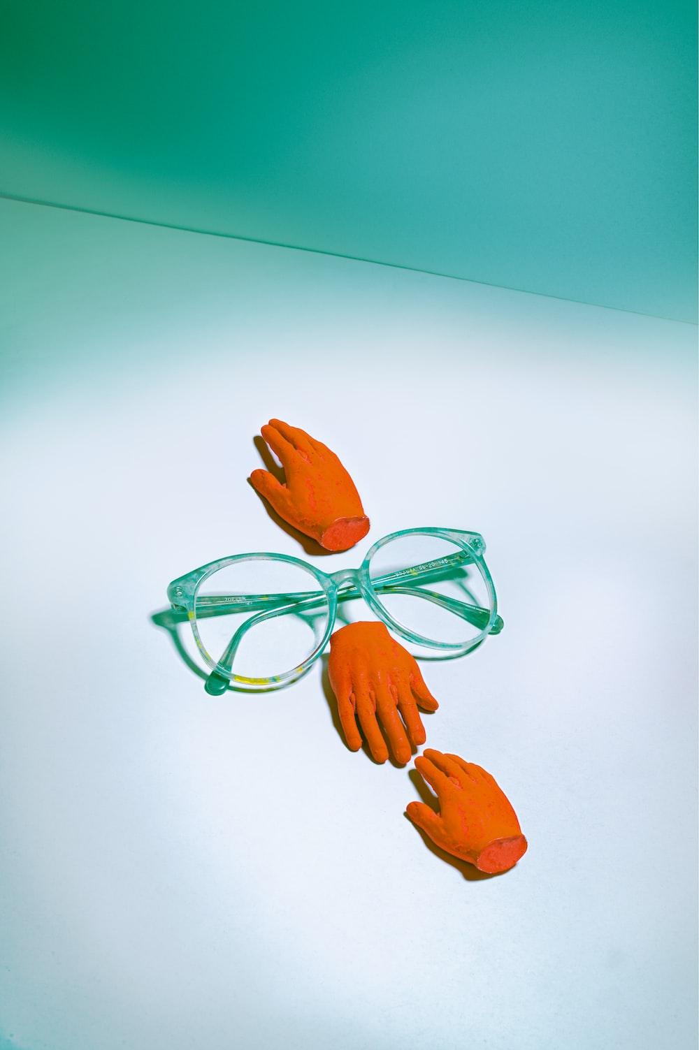 green framed eyeglasses beside orange rose