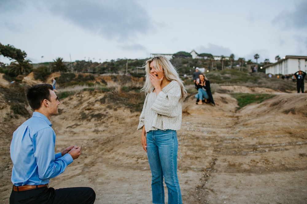 woman in white long sleeve shirt and blue denim jeans standing on brown sand during daytime