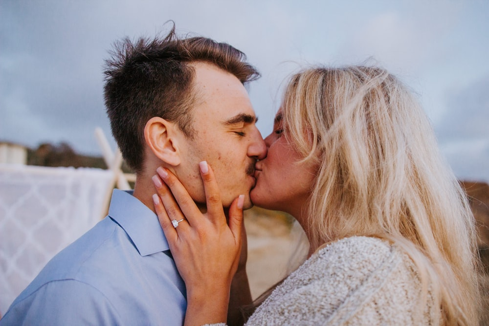 man in blue dress shirt kissing woman in white knit sweater