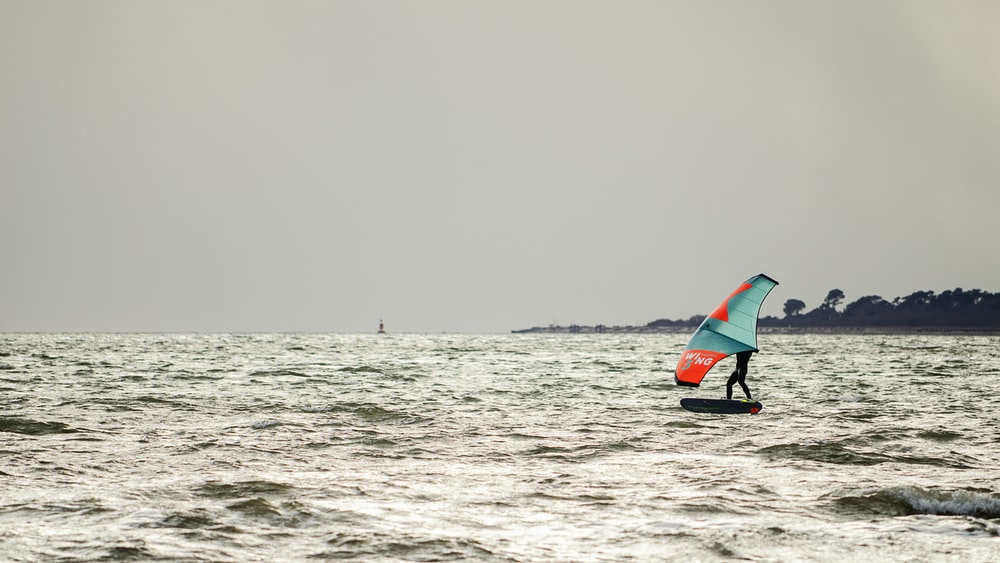 person in black wet suit riding red and black surfboard on sea during daytime