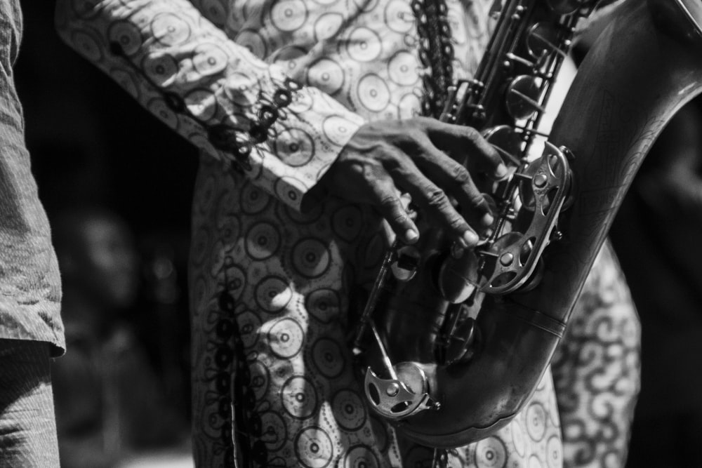 grayscale photo of person playing saxophone