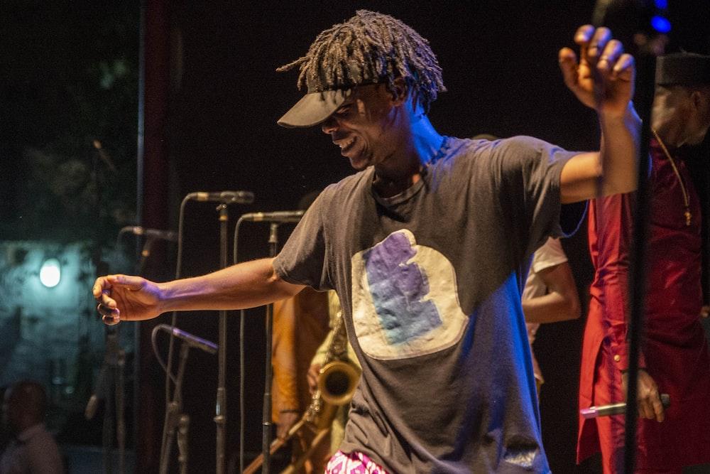 man in grey t-shirt playing saxophone