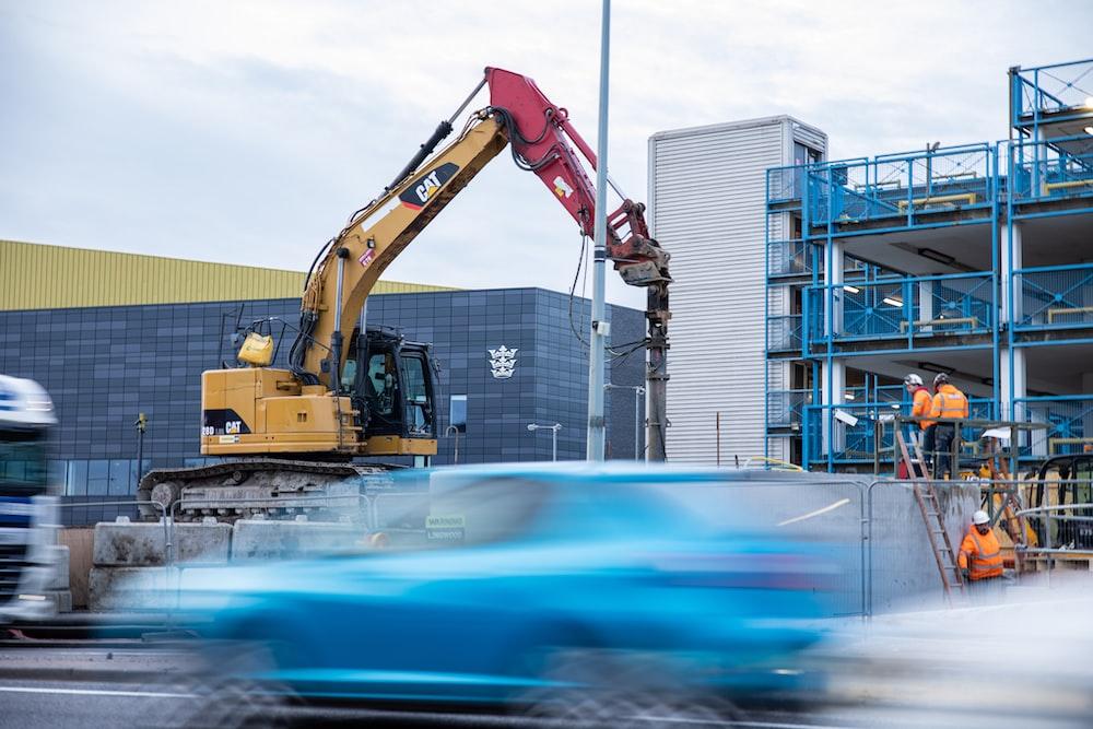yellow and black heavy equipment near building