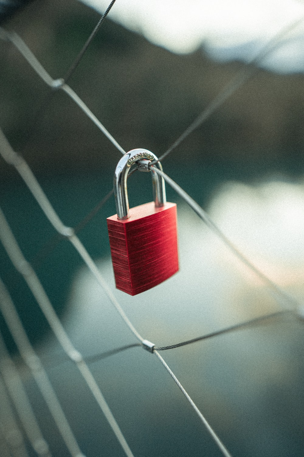 red padlock on gray wire fence