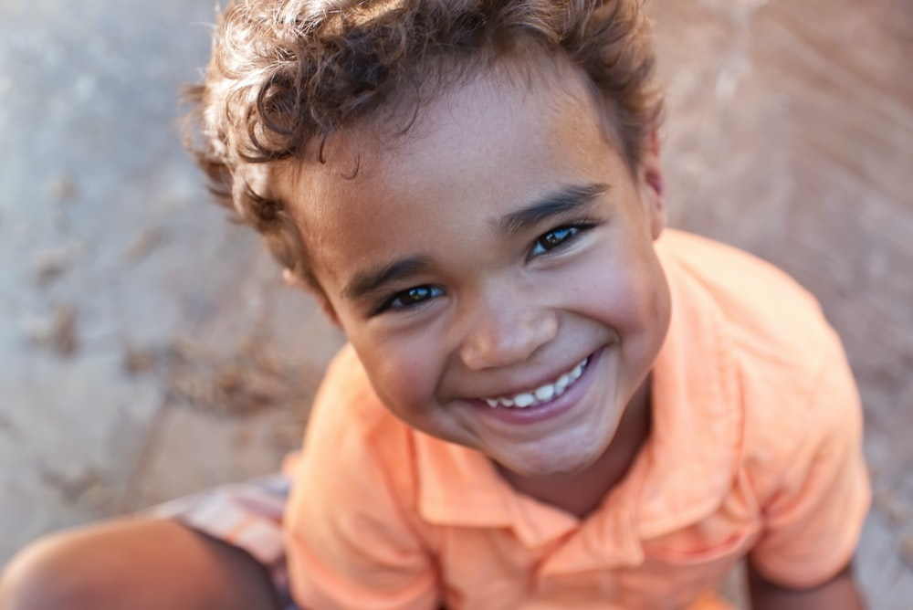 boy in orange polo shirt smiling
