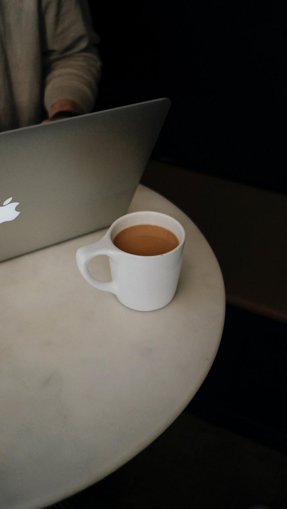 white ceramic mug on silver macbook