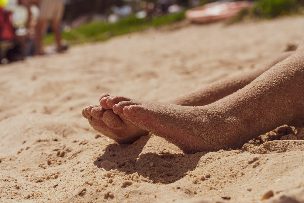 persons feet on brown sand during daytime