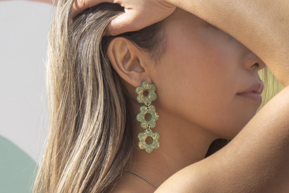 woman wearing silver and green flower earring