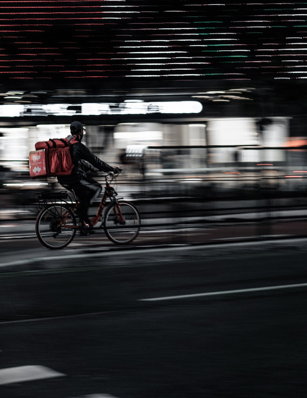 man in red jacket riding bicycle in the city