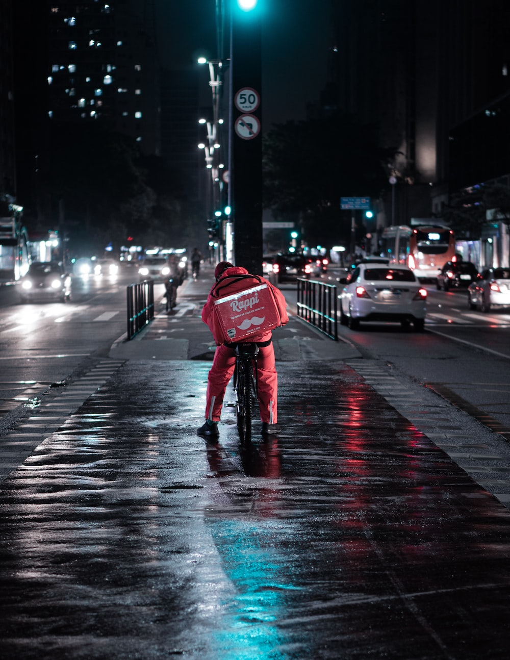 person in red jacket and blue denim jeans walking on street during night time