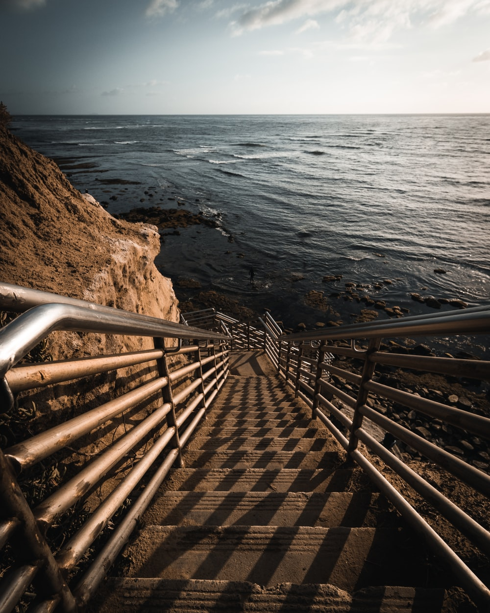 brown wooden stairs on brown rocky beach