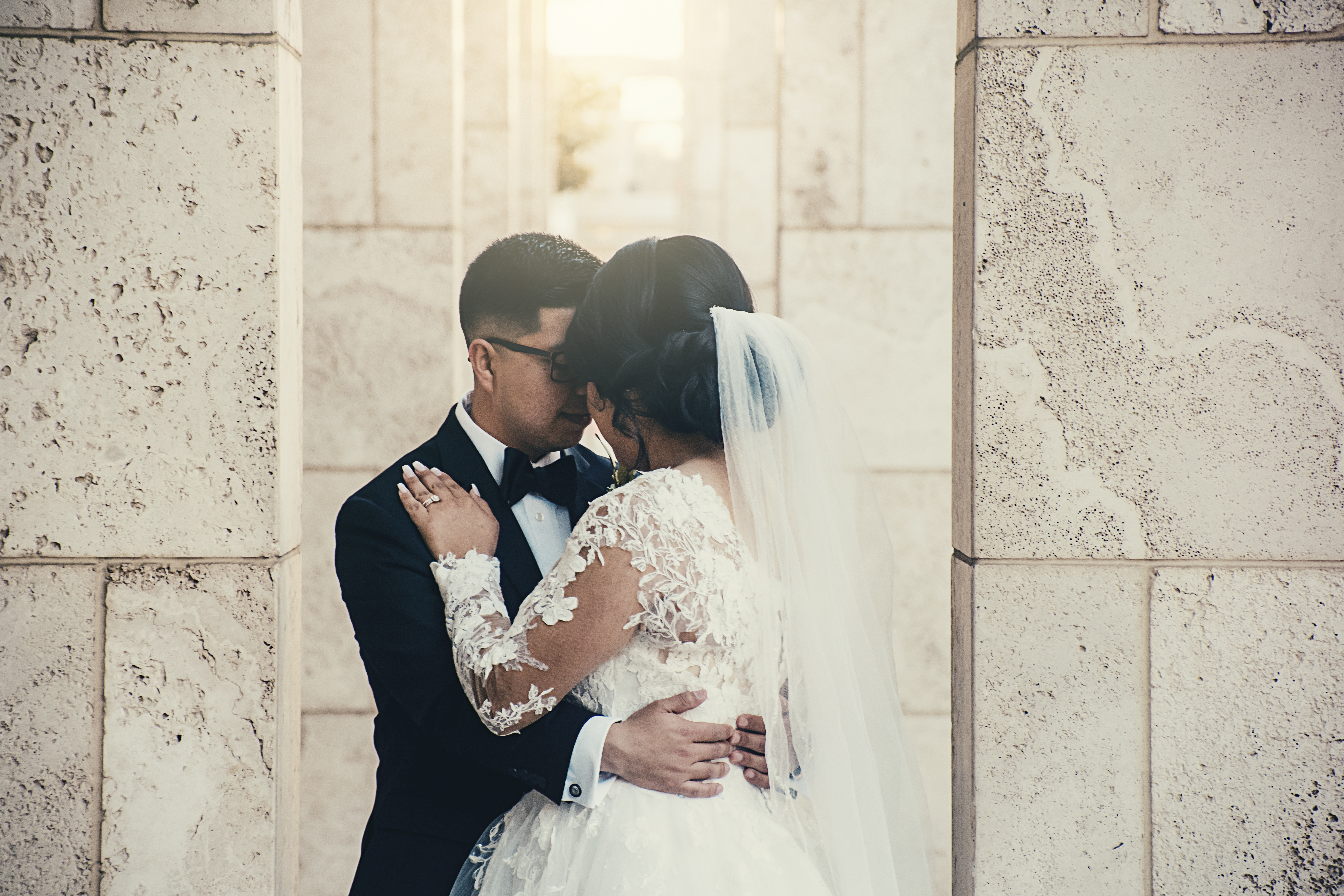 bride and groom standing near white wall