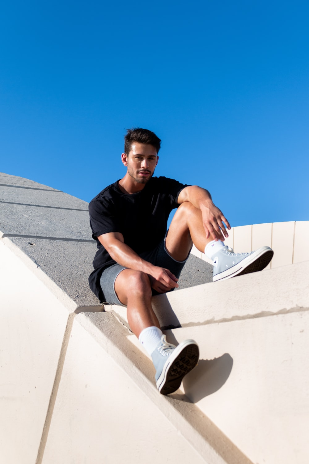 man in black crew neck t-shirt sitting on white concrete wall during daytime