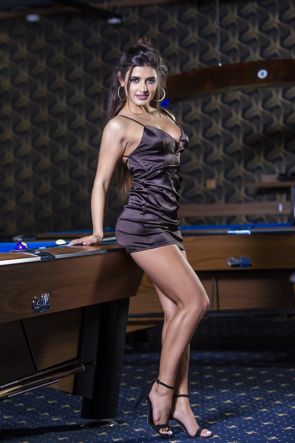 woman in black spaghetti strap dress standing beside brown wooden table