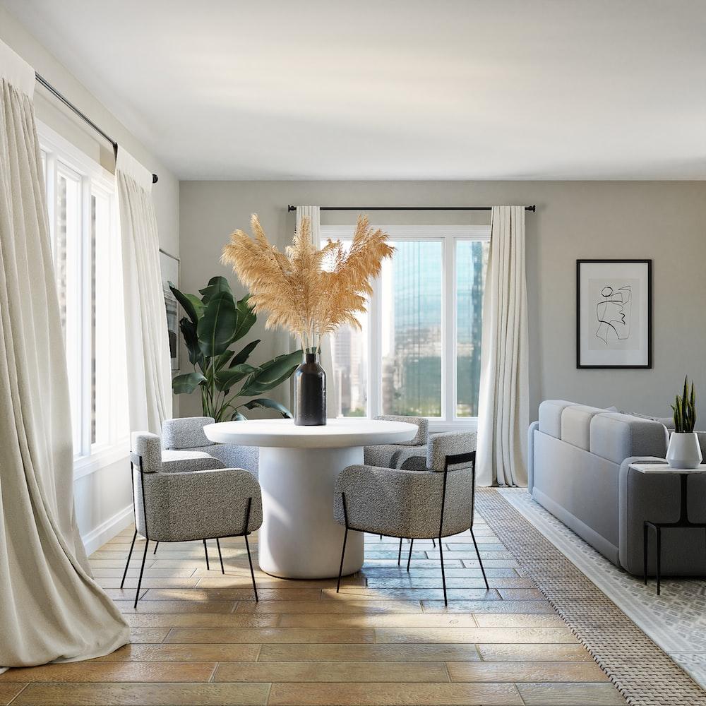 white and gray sofa chairs near white window curtain