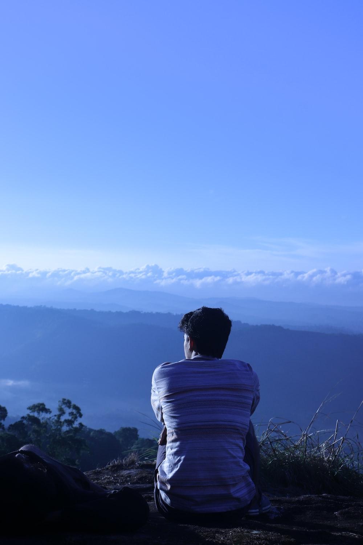 man in white shirt sitting on rock looking at mountains during daytime