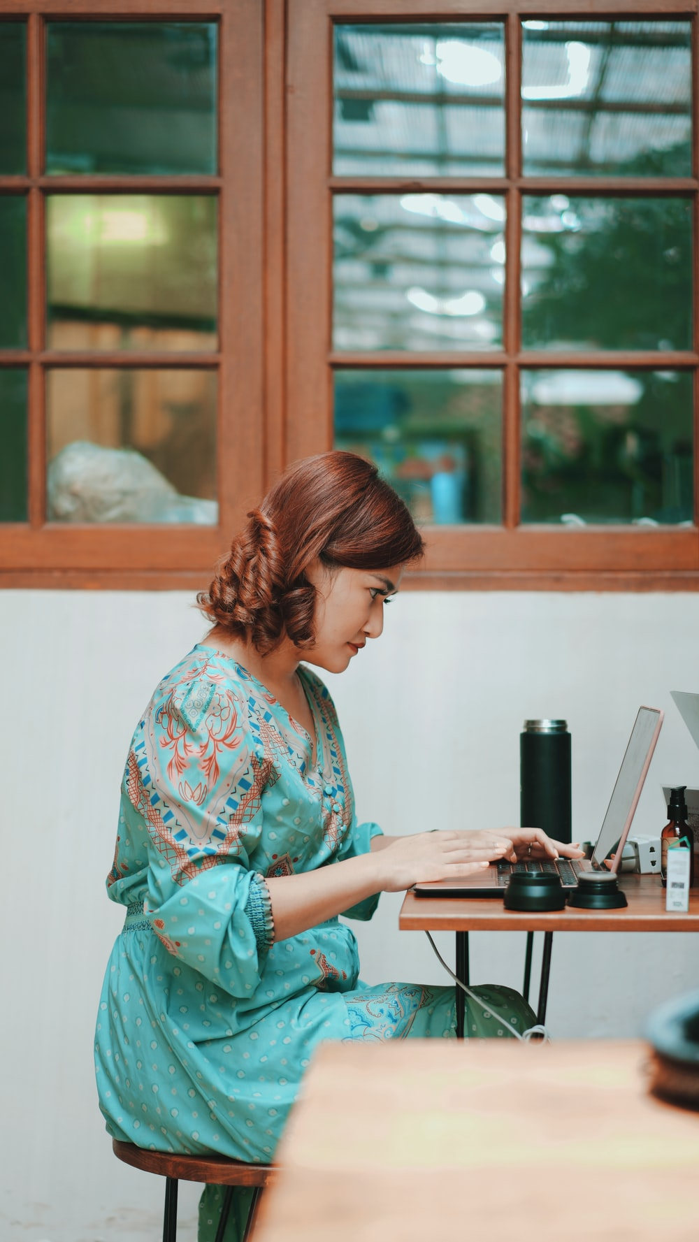 woman in green and white floral long sleeve shirt using computer