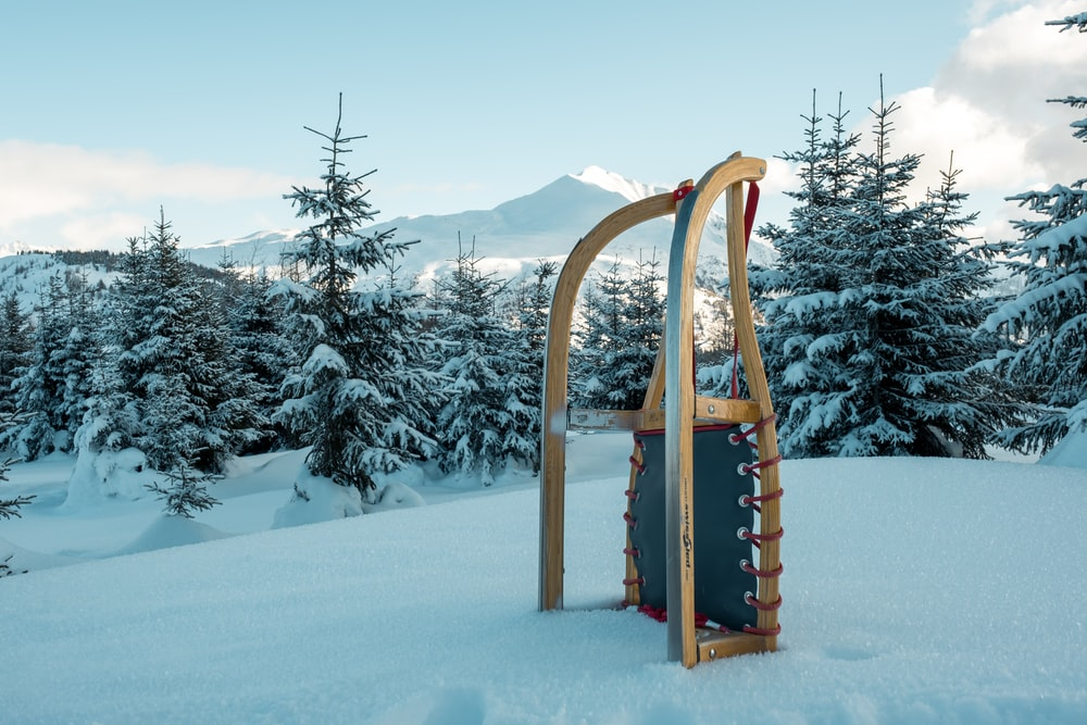 brown wooden snow sled on snow covered ground during daytime