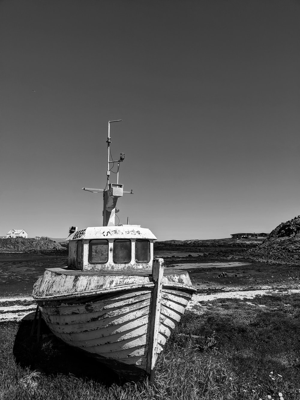 grayscale photo of boat on beach