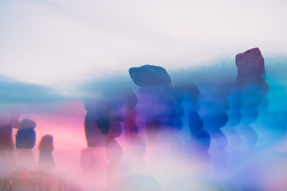 silhouette of 3 person standing on rock formation