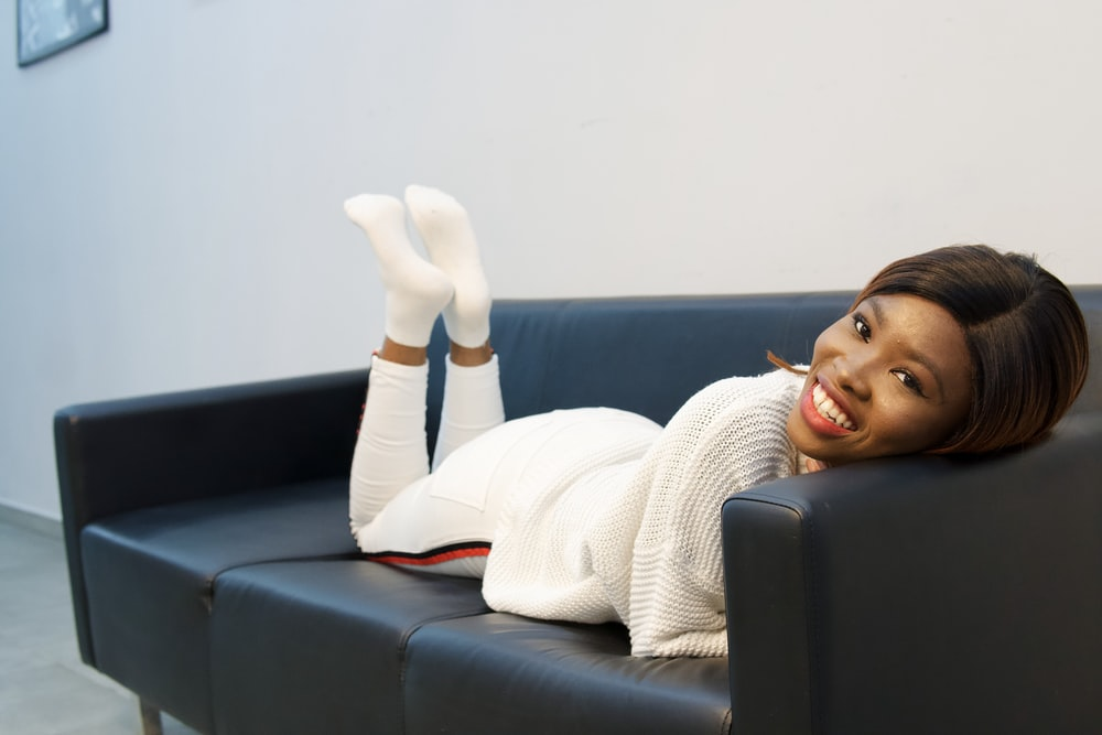woman in white sweater lying on black couch