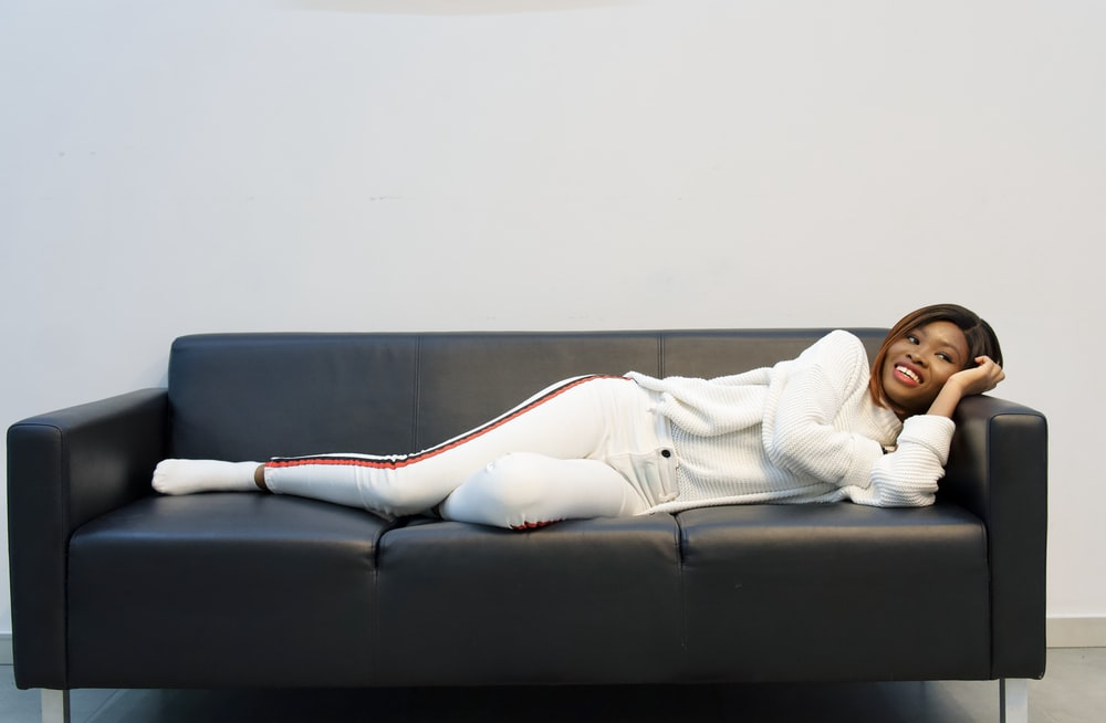 woman in white long sleeve shirt lying on black couch