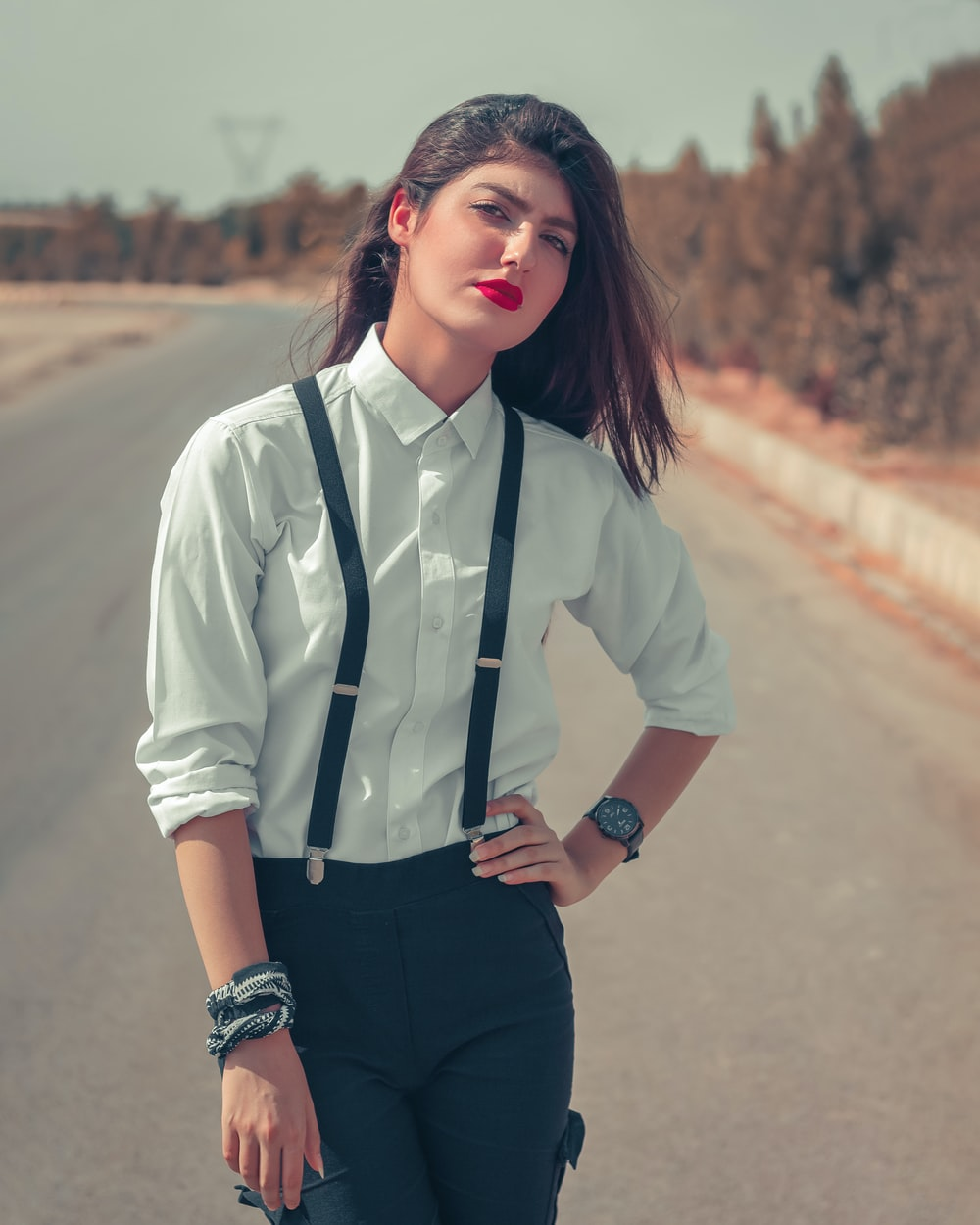 woman in white button up shirt and black pants standing on road during daytime