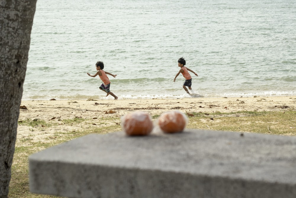 3 boys playing soccer on beach during daytime