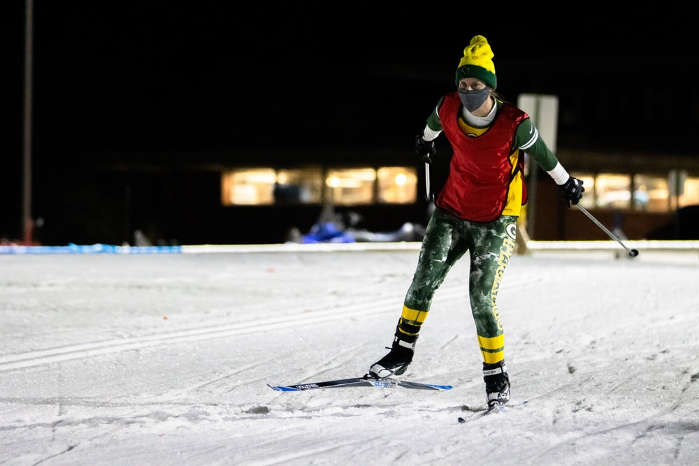 person in red and black jacket and green pants riding on snow board during daytime