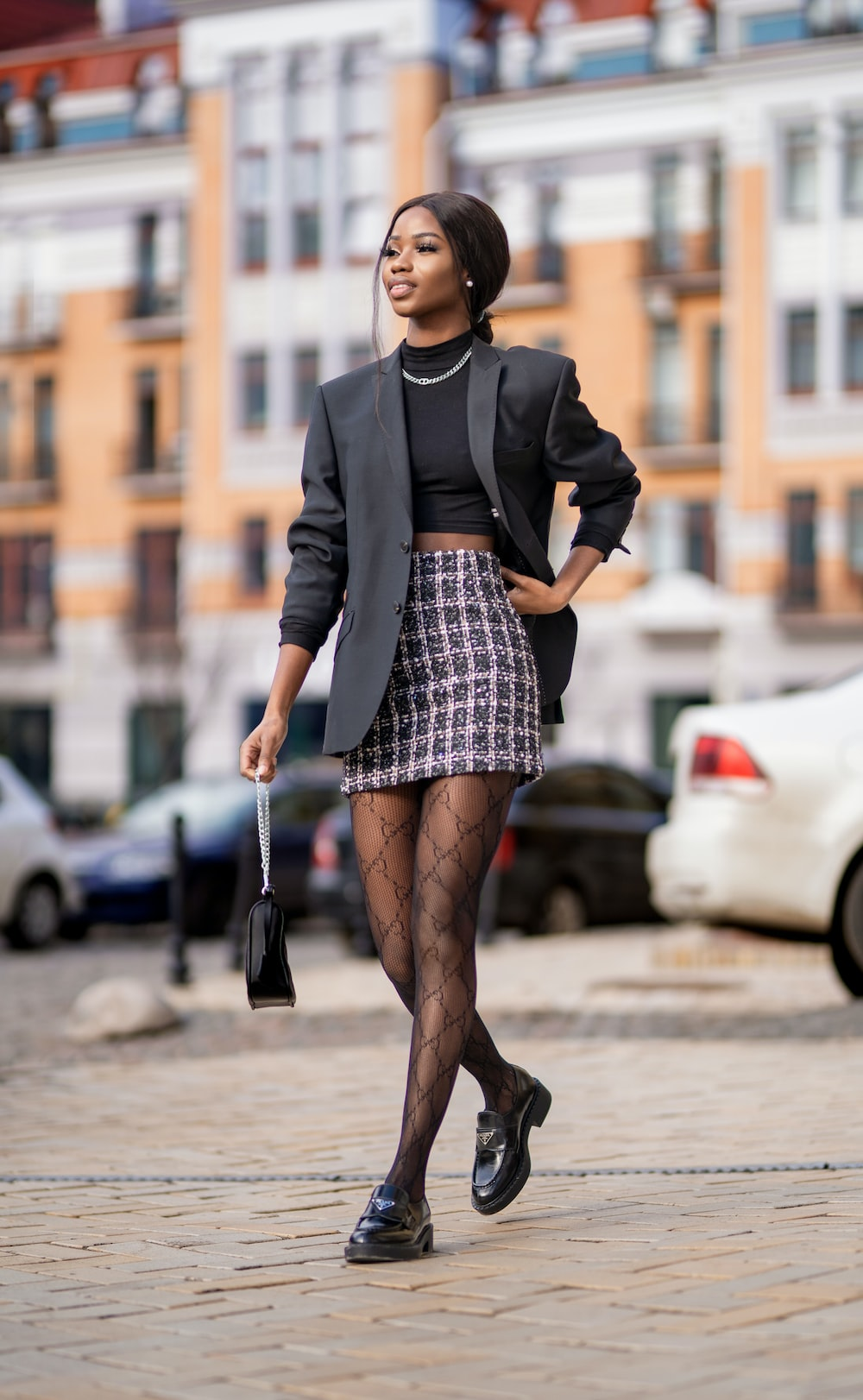 woman in black long sleeve shirt and brown skirt standing on sidewalk during daytime
