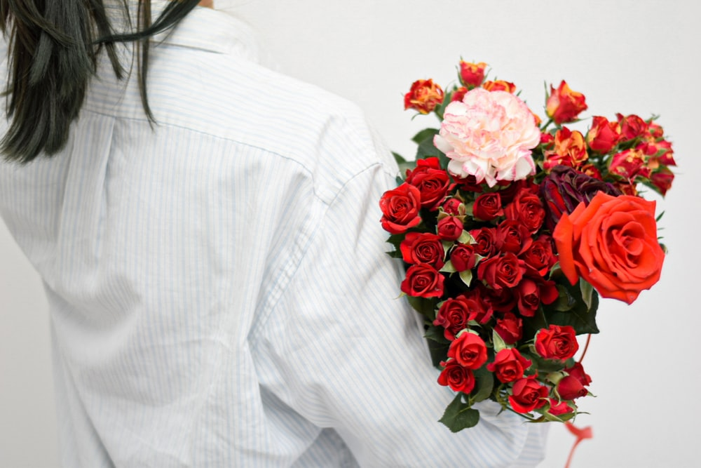 woman in white long sleeve shirt holding red roses