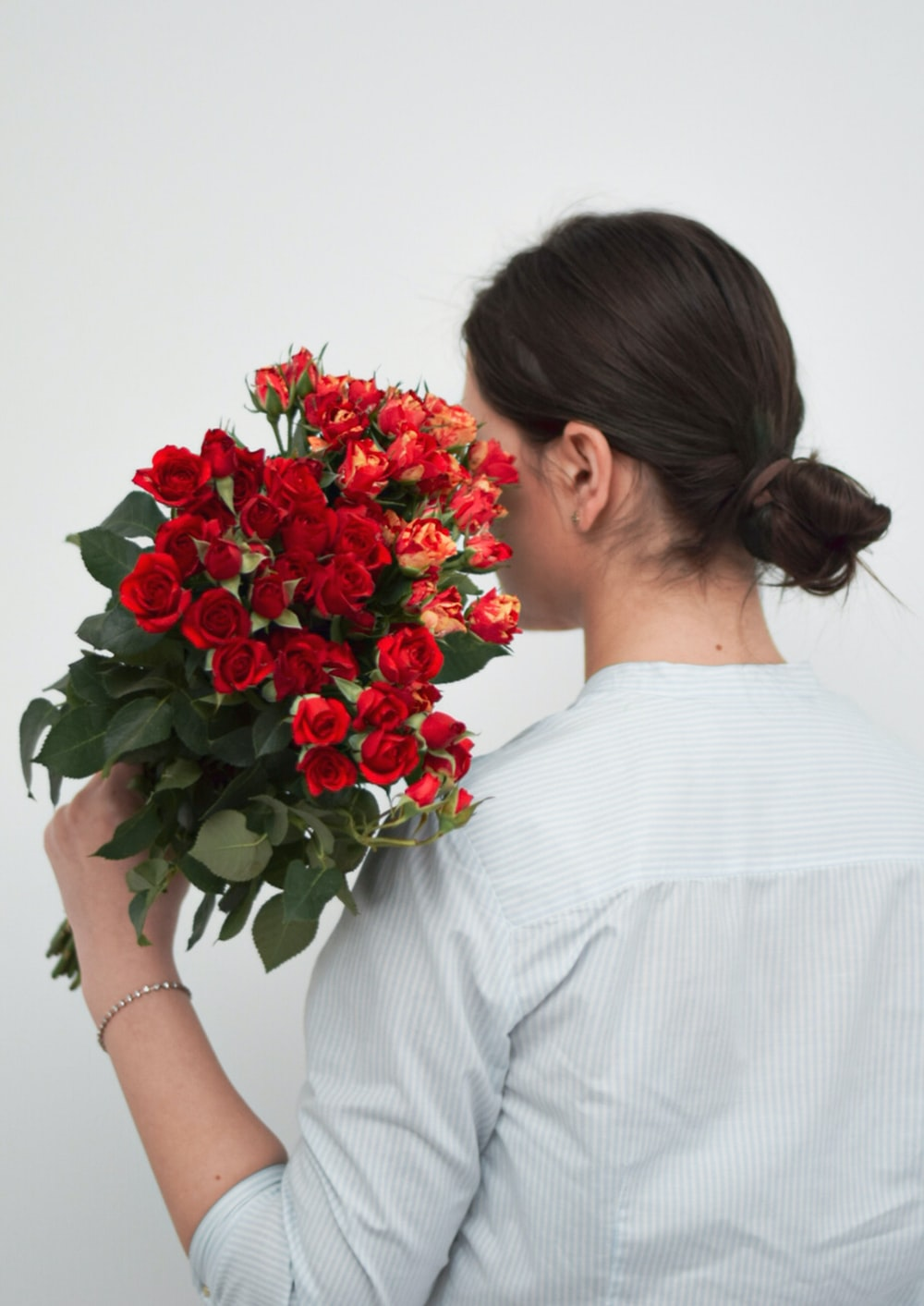 woman in white dress holding red roses