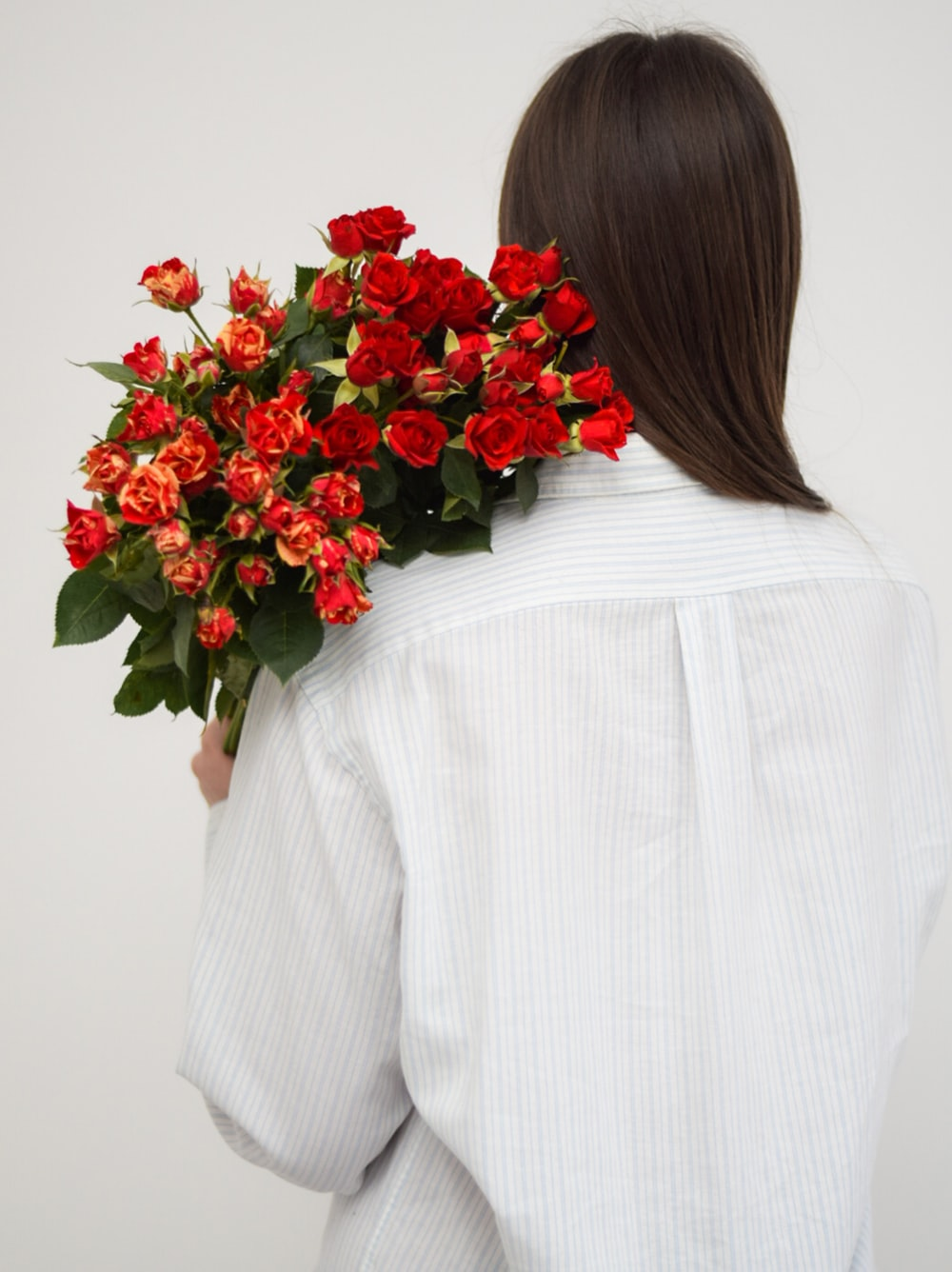 woman in white long sleeve shirt holding red rose bouquet